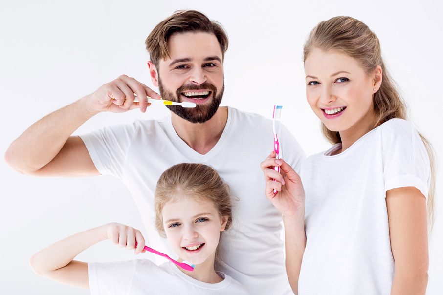 family smiling and brushing